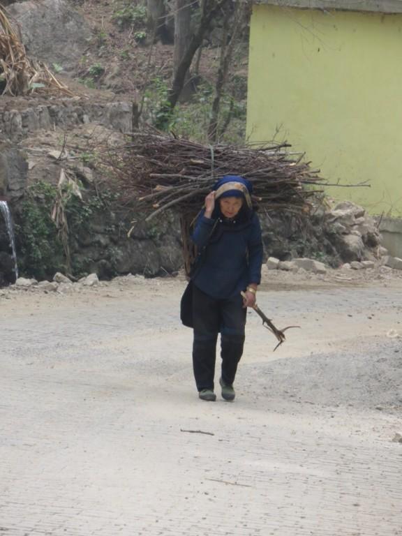 Femme Hani portant de petits bois